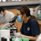 students wear masks and look through microscopes in a lab