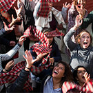 group of people looking in the air with hands up