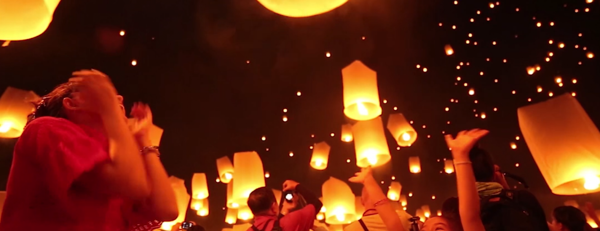 people letting go of lanterns into the air