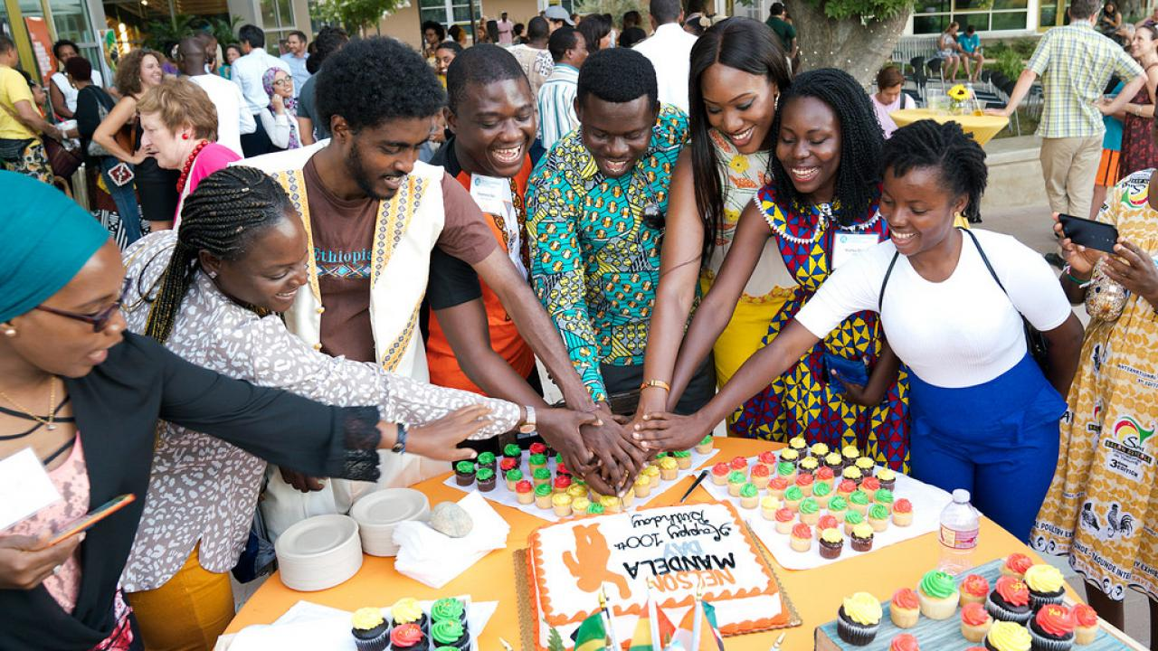 group of people with cake celebrating mandela day