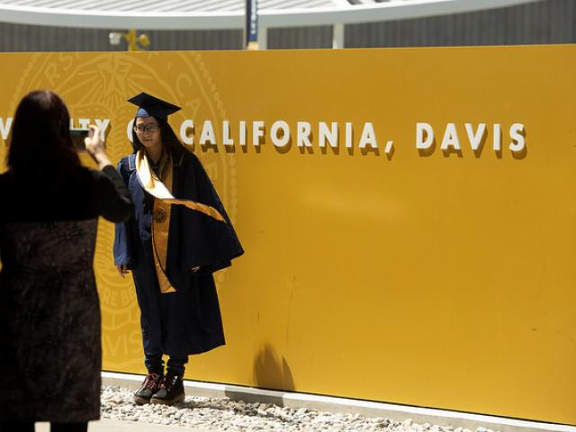 girl standing in front of uc davis welcome sign in graduation gown