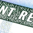 magnifying glass over green card, says permanent resident