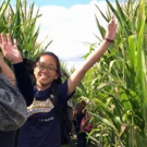students jumping in a corn field