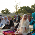 women sitting with their heads covered, talking