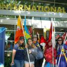 women with international flags in front of the international center