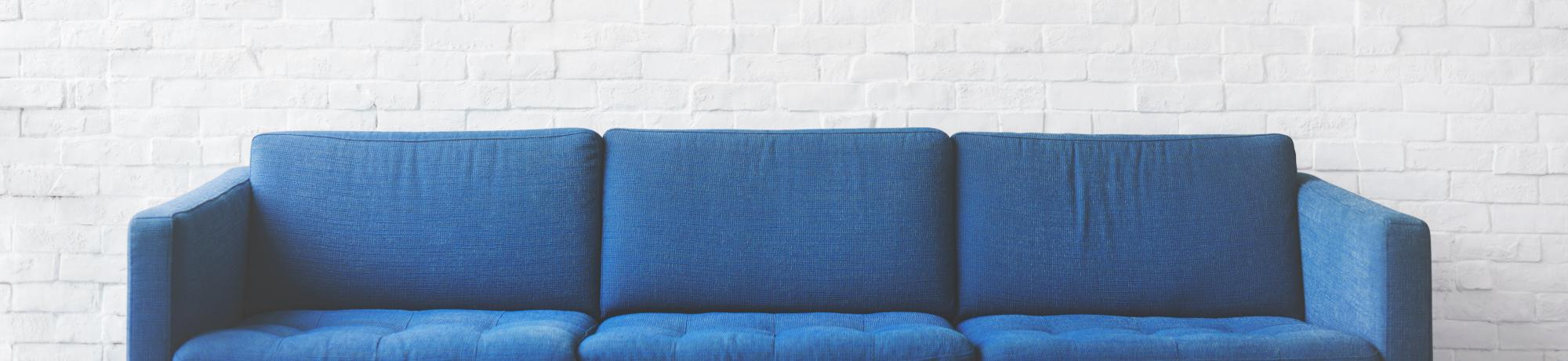 blue couch against white wall