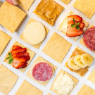 crackers with different toppings like banana and strawberry and salami